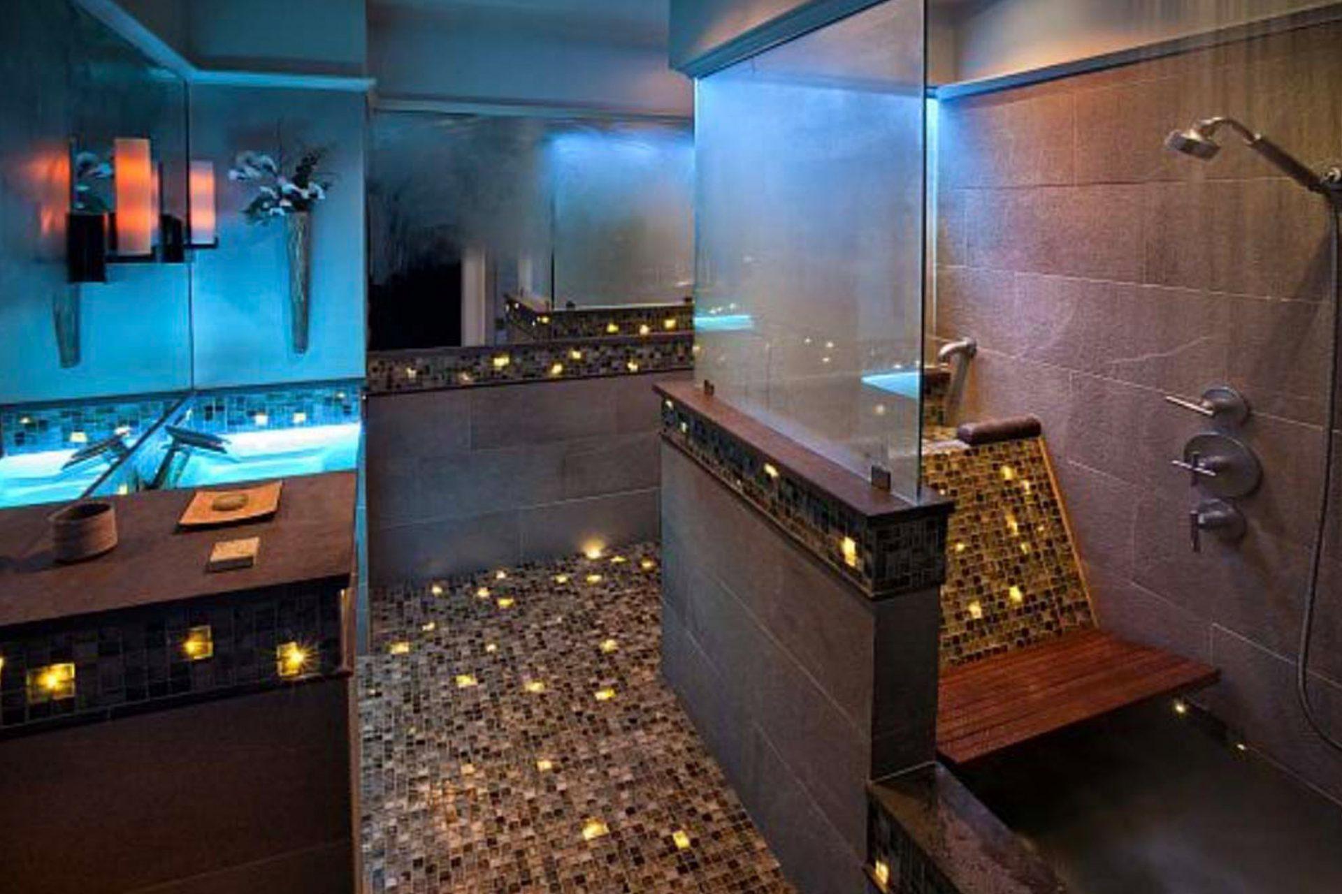 A luxurious bath with colorful fiber optic lighting, blue-lit glass sink, a roman bath and a rain head shower.