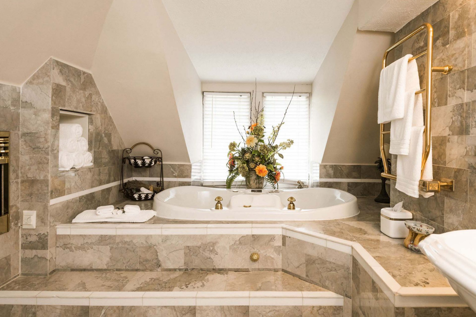 A luxurious white marble bathroom with heated floors and an elevated two-person Whirlpool bathtub, part of a 5-room suite in an Asheville bnb.