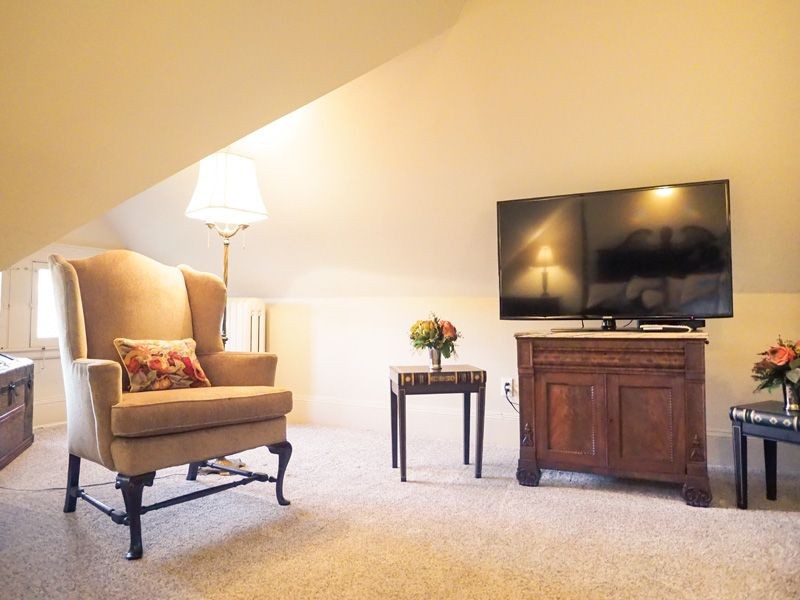 A relaxing corner in the attic with a TV, armchair, standing lamp and two small side tables.