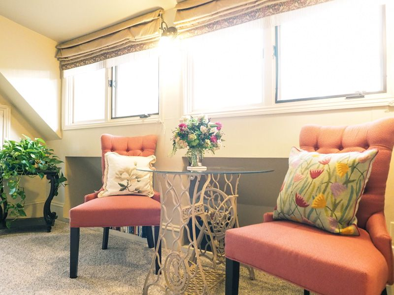 A relaxing area at one of the suites in the Asheville bed and breakfast. Two armchairs with floral pillows with a table and a flower bouquet.