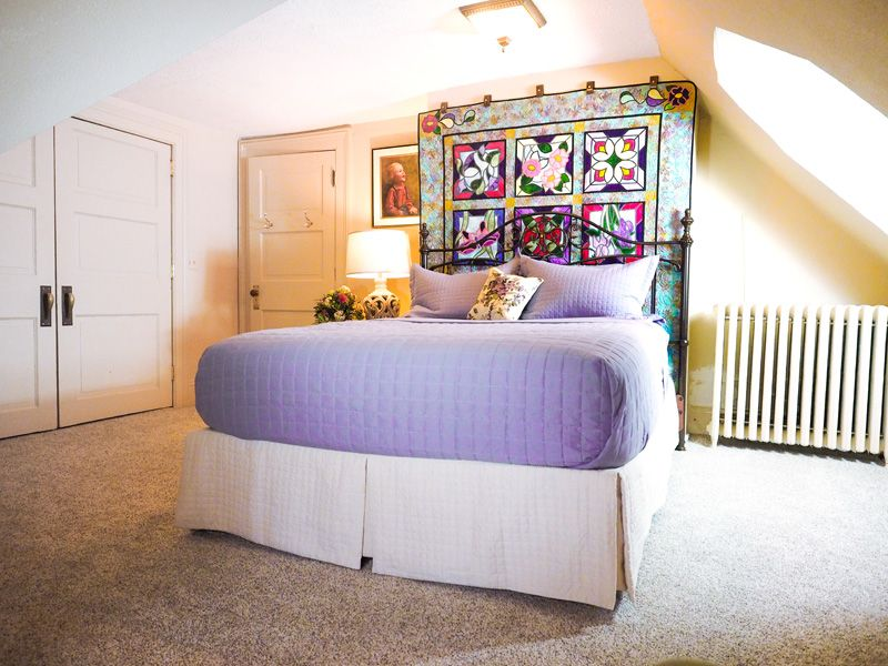 A bright, beige room with a queen bed with purple linen and a quilt hanging on the wall at the head of the bed.