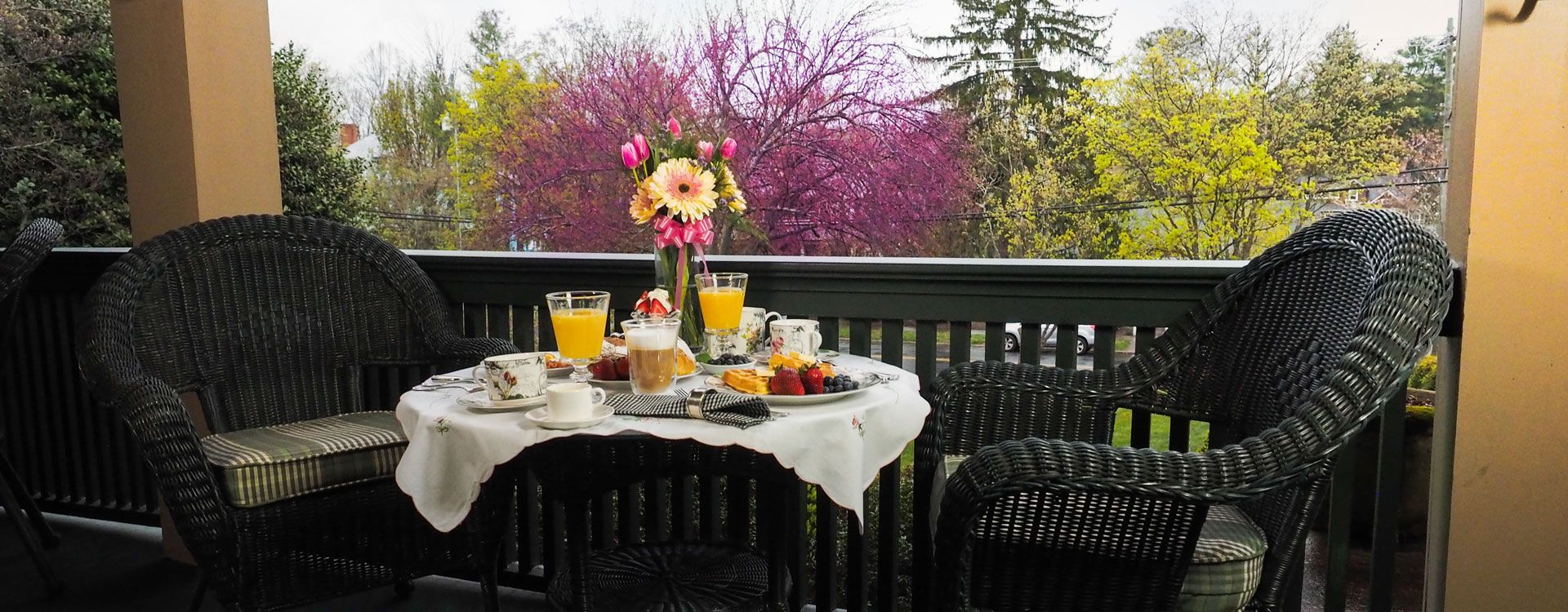 Breakfast served on the porch. A table set for two with a white tablecloth. Waffles with fruits, two glasses of orange juice and a coffee.