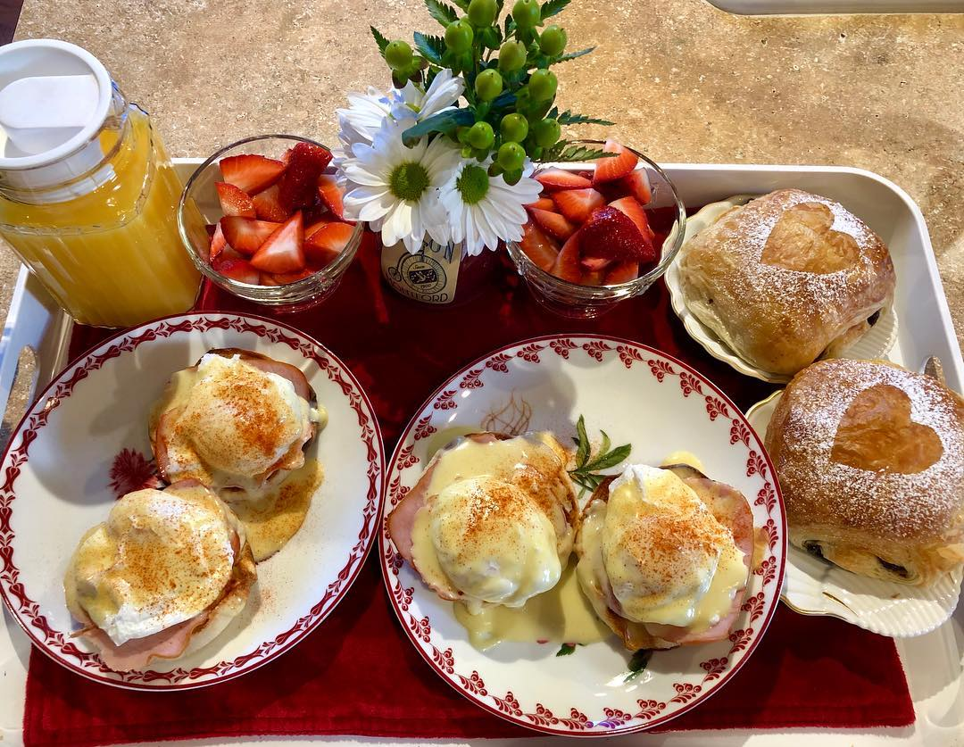 Breakfast at the Asheville BnB. A tray with Eggs Benedict, homebaked buns, two bowls with strawberries and a jug of orange juice.