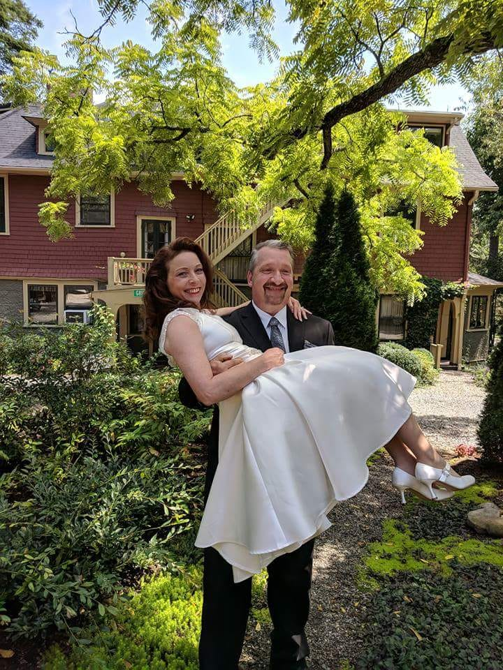 Elopement in Asheville NC. A newly wed couple, the husband is carrying the wife through the backyard garden of the Inn.