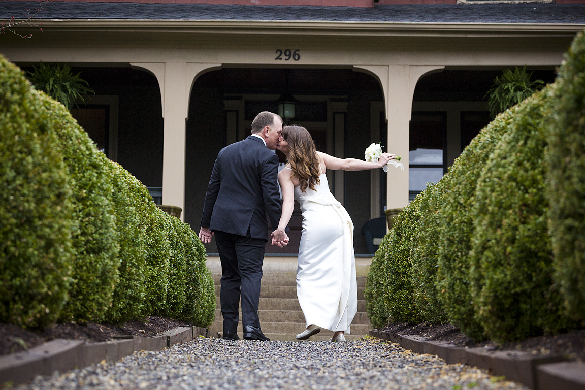 Asheville NC Elopement. A couple holding hands and kissing on the way to the main entrance of Inn on Montford.