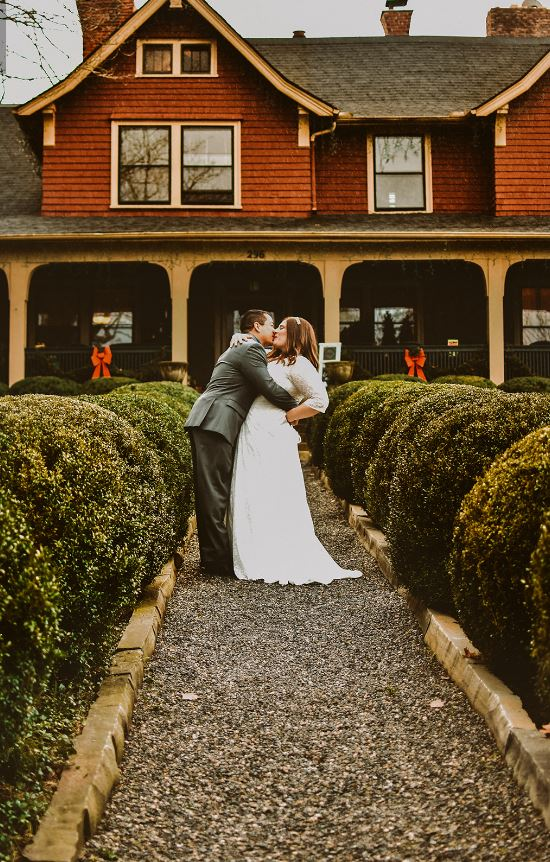An Asheville elopement. A newly wed couple kissing on the gravel path leading to the front entrance of the Inn on Montford.