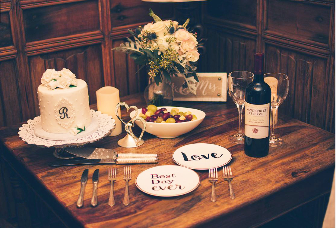 An intimate wedding in Asheville. A corner table with a small wedding cake, wedding bouquet, wine bottle, two wine glasses, fruit bowl, plates and cuttlery.