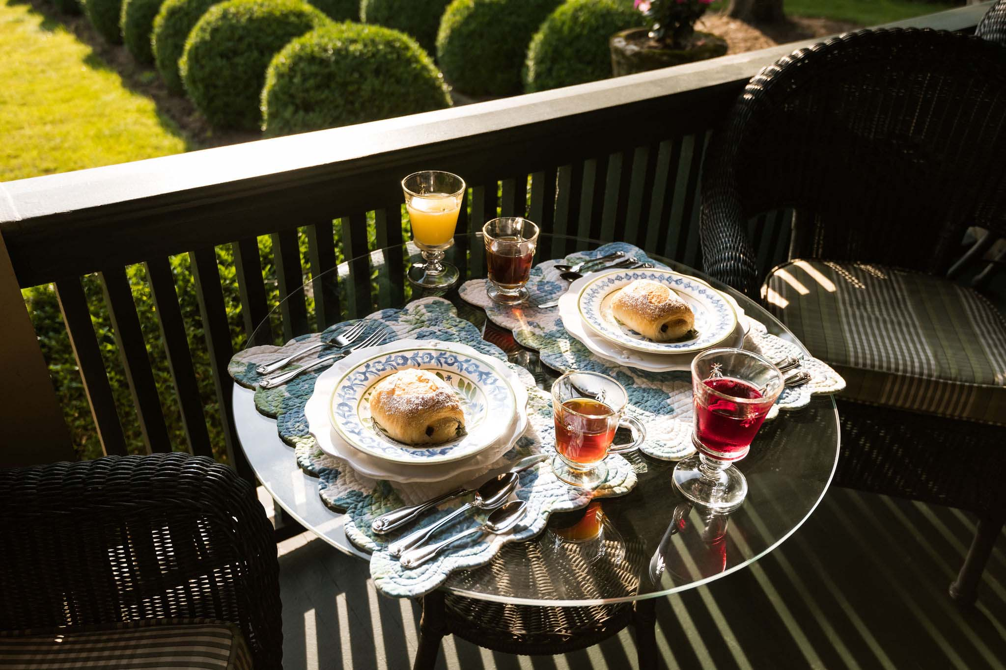 Breakfast served on the porch. A table for two with floral placemats with ceramic dishes and cuttlery, two glasses of juice, two glasses of tea and two home-baked buns.