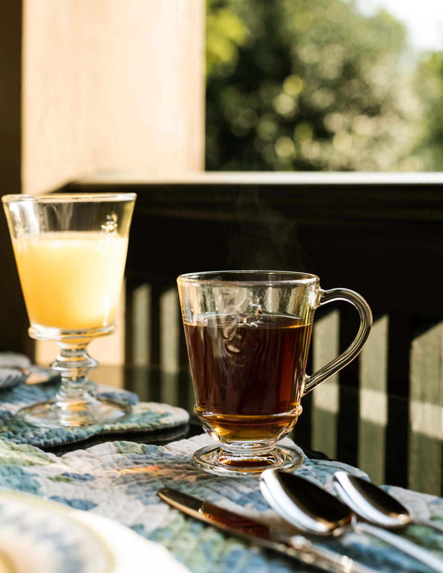 A close-up of a short glass with tea and a longer glass with orange juice.