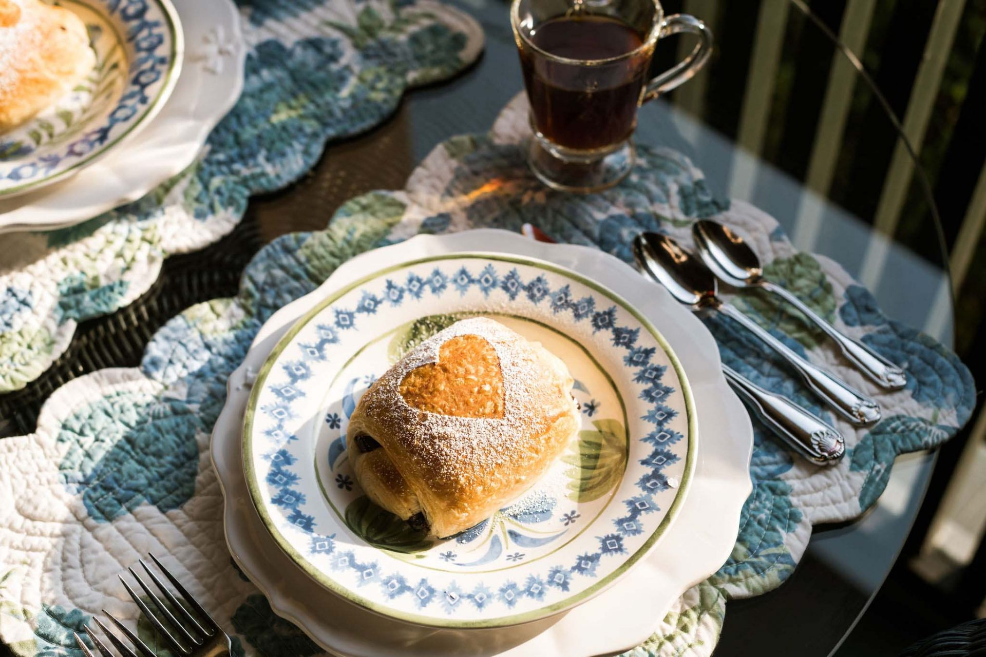 A close-up of a home-baked bun with a heart shaped from caster sugar. A floral placemat, set of cuttlery, and a glass with tea.