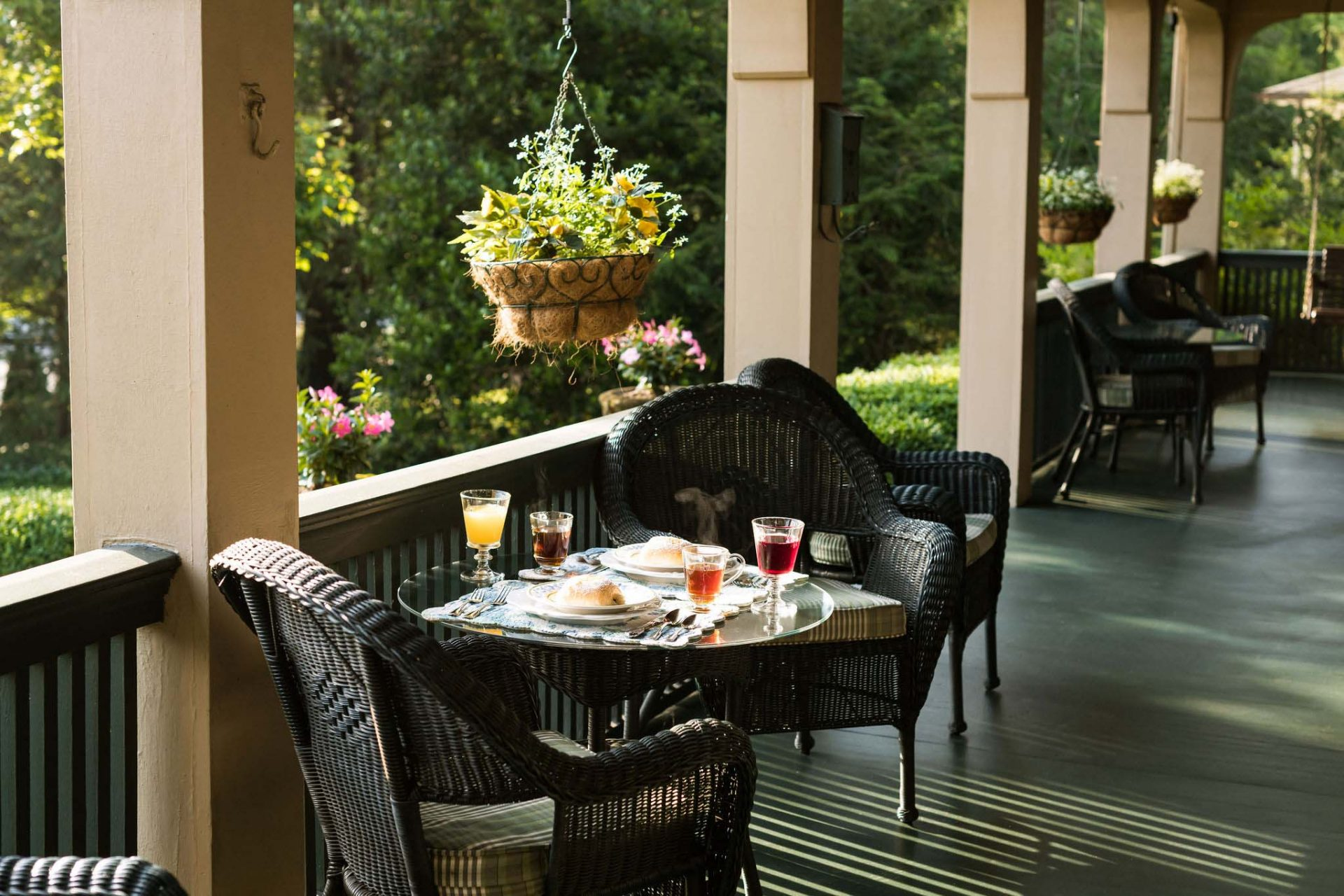 Outdoor breakfast on the bnb's porch. Rattan chairs with a table set for two. A yellow pot hanging from one of the Inn's arches.
