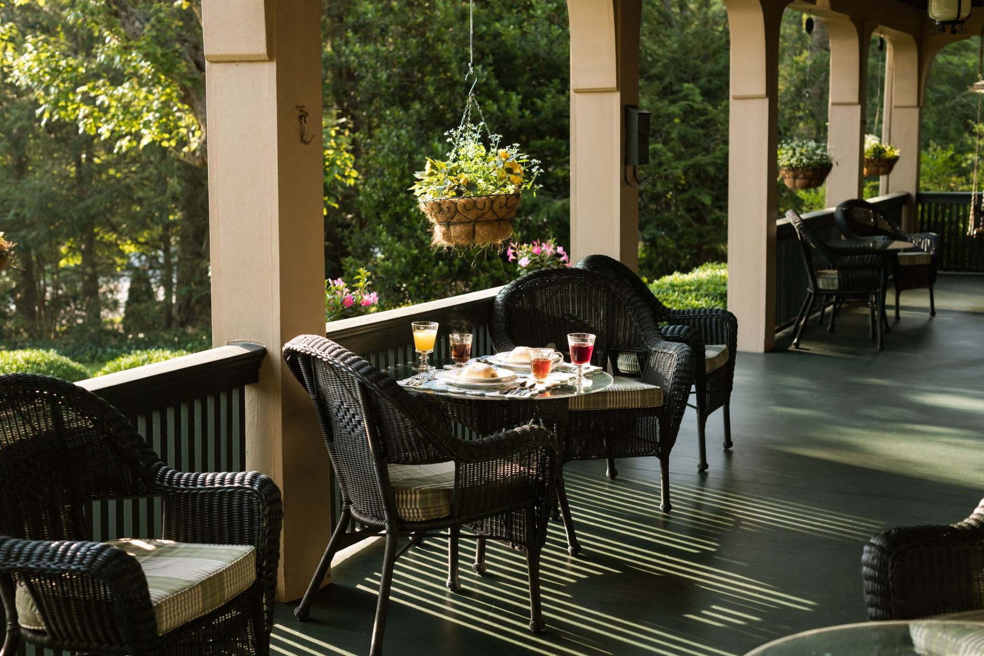 Breakfast served on the porch. A row of rattan tables and chairs. In the background green bushes, flowers hanging in pots from the porch's ceiling.