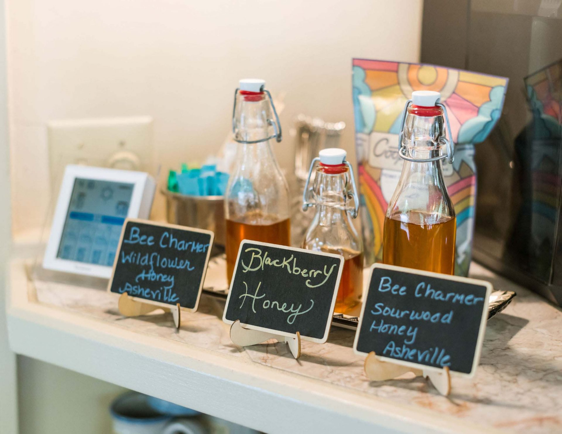 3 glass bottles of locally made honeys with tags describing the flavors - wildflower honey, blackberry honey, and sourwood honey. In the background a bag of coffee beans, sugar, and spoons.