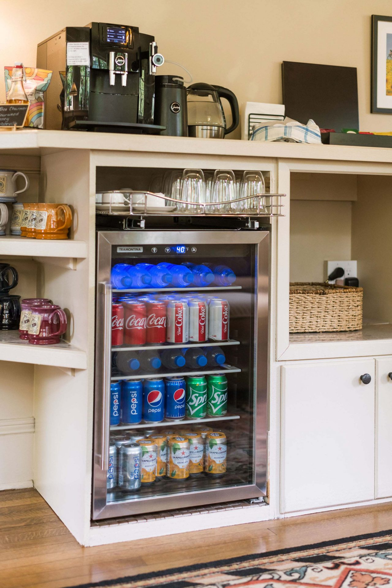 Amenities at guests' disposal - a fridge with beverages, a coffee maker, colorful ceramic mugs, water boiler, and a selection of teas.