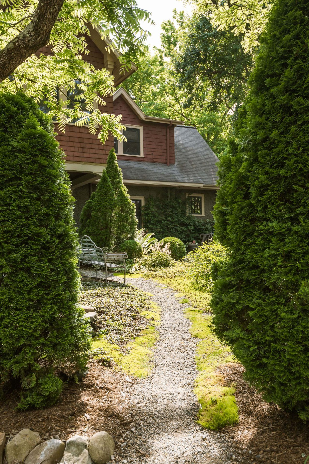 A narrow gravel path leading through the backyard garden to the carriage house.