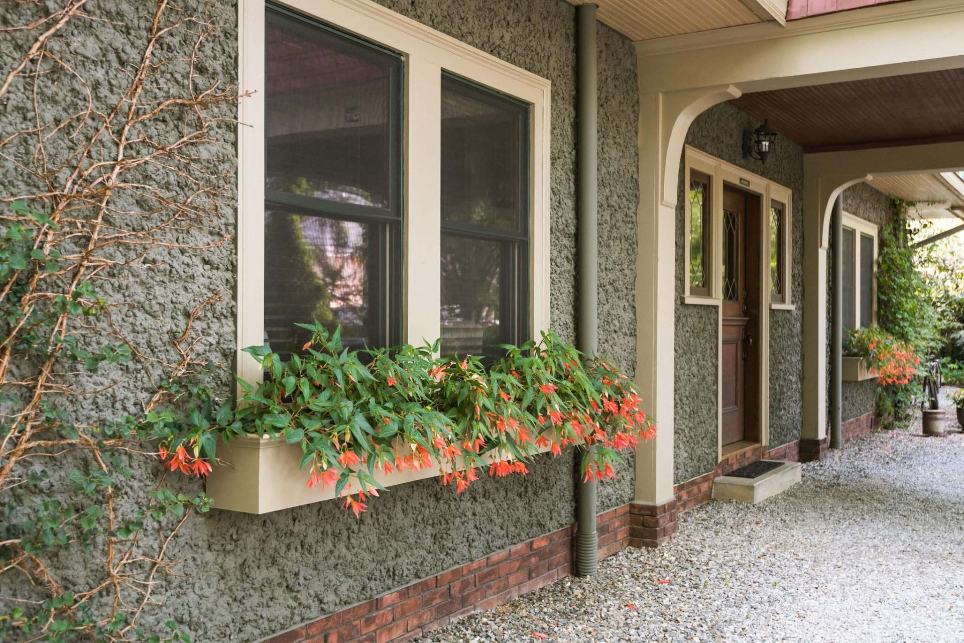 Entrance to the cloister suite in the carriage house. A grey wall with windows on each side of the door, window box planters with red flowers.