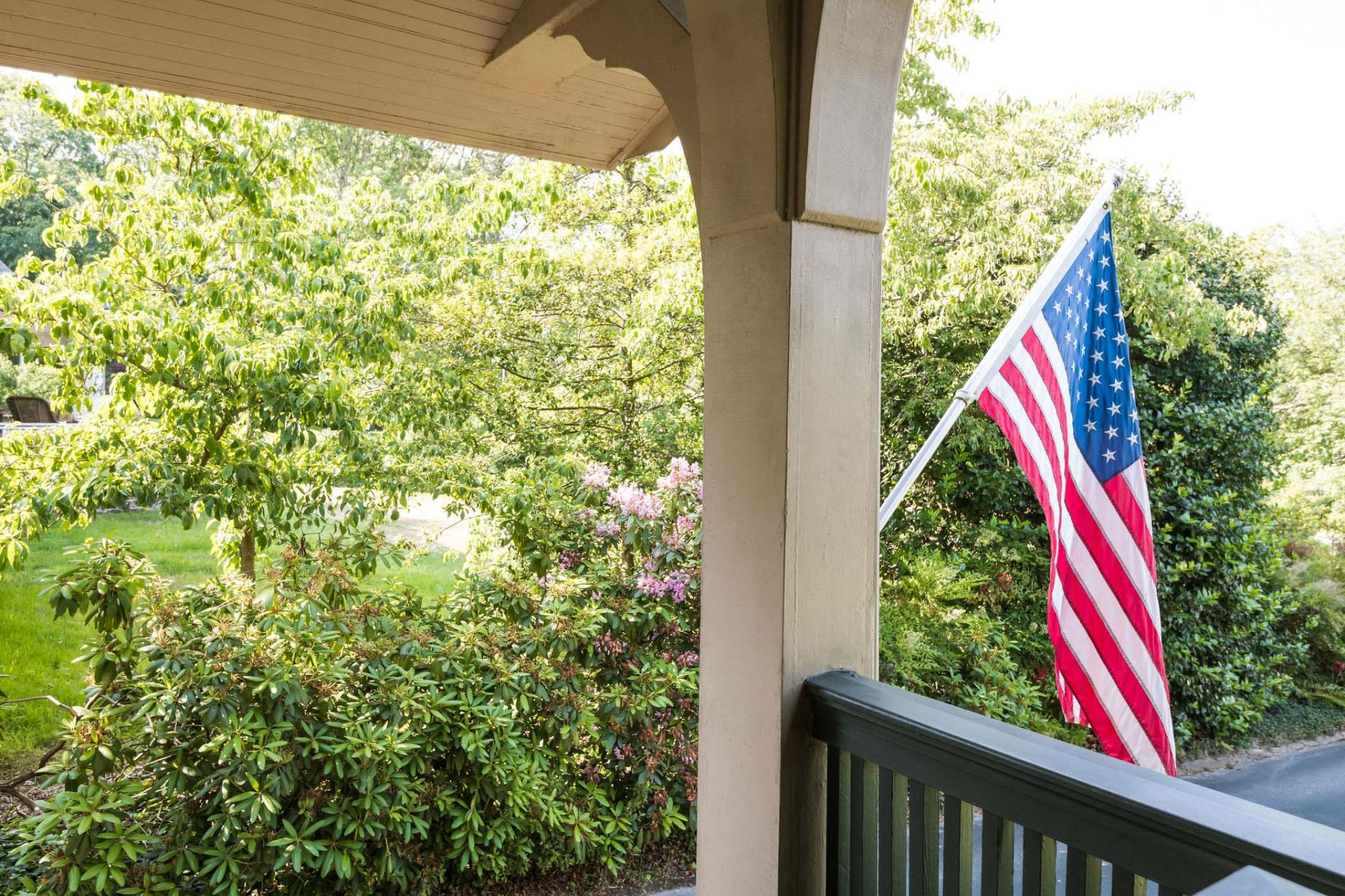 An American flag hanging at the end of the porch, with green bushes and trees in the background.