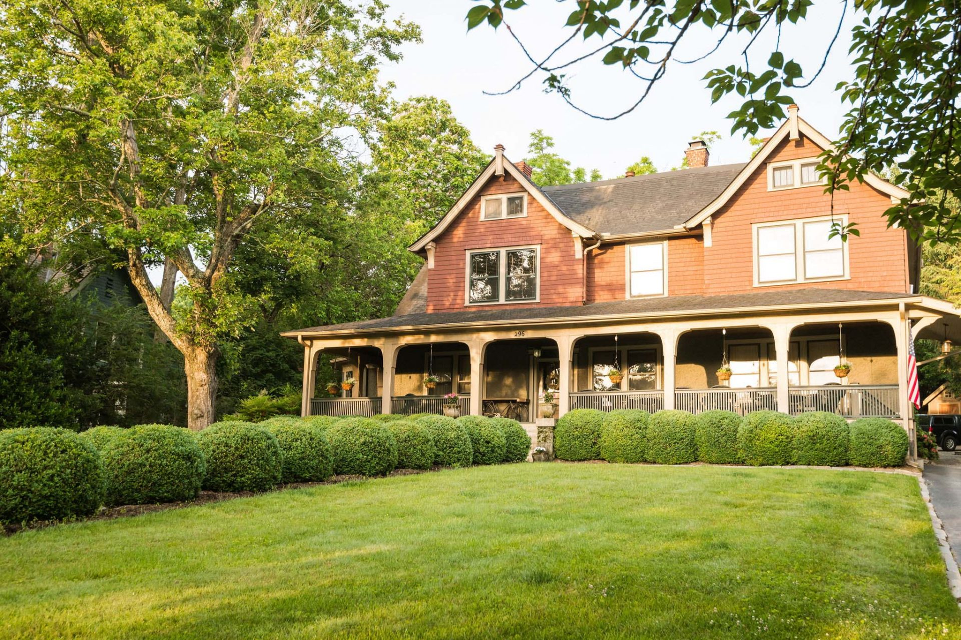 The front facade of the Asheville bed and breakfast. A grass front yard with two rows of round ball bushes. A long, arched porch with planters hanging from the arches.