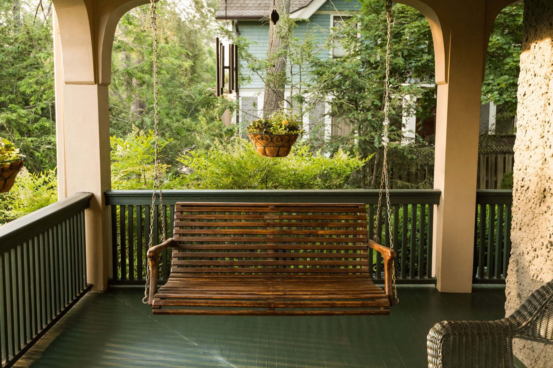 A wooden porch swing hanging at the far end of the porch painted in dark green, with green bushes and trees in the background.