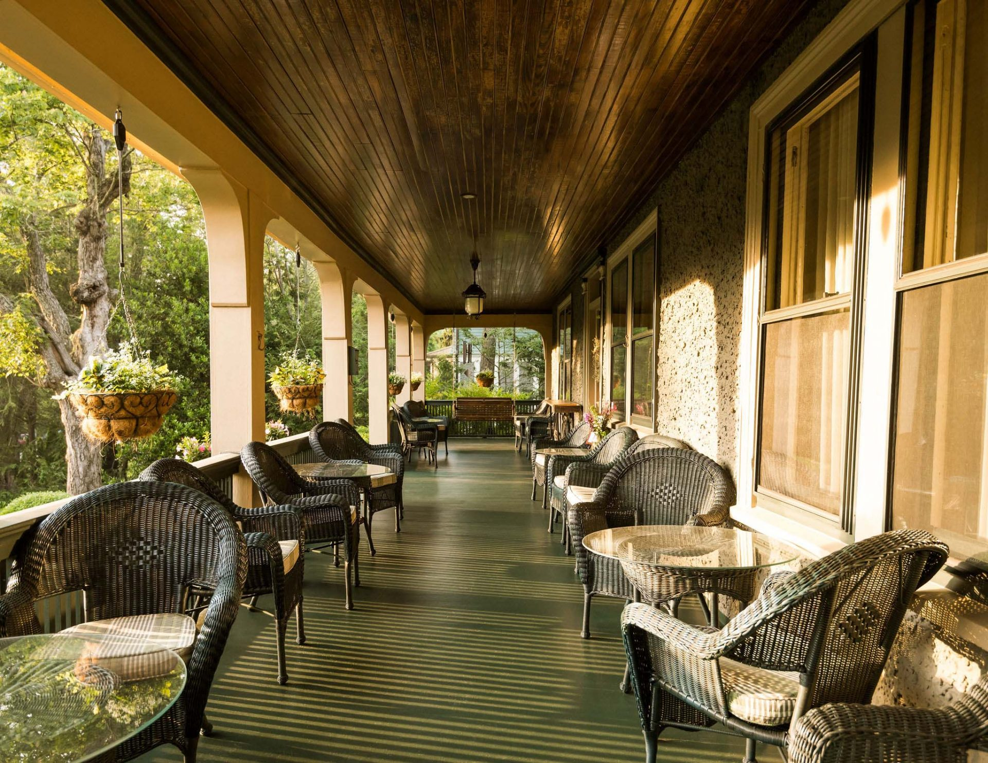 The front porch of the Inn with a wooden brown ceiling and two rows of rattan chairs and tables.