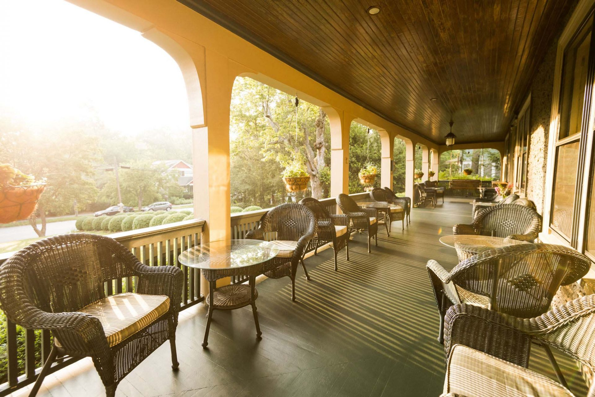 The front porch of the Inn lit by warm, afternoon sun. Two rows of tables and rattan chairs with planters hanging from the porch's arches.
