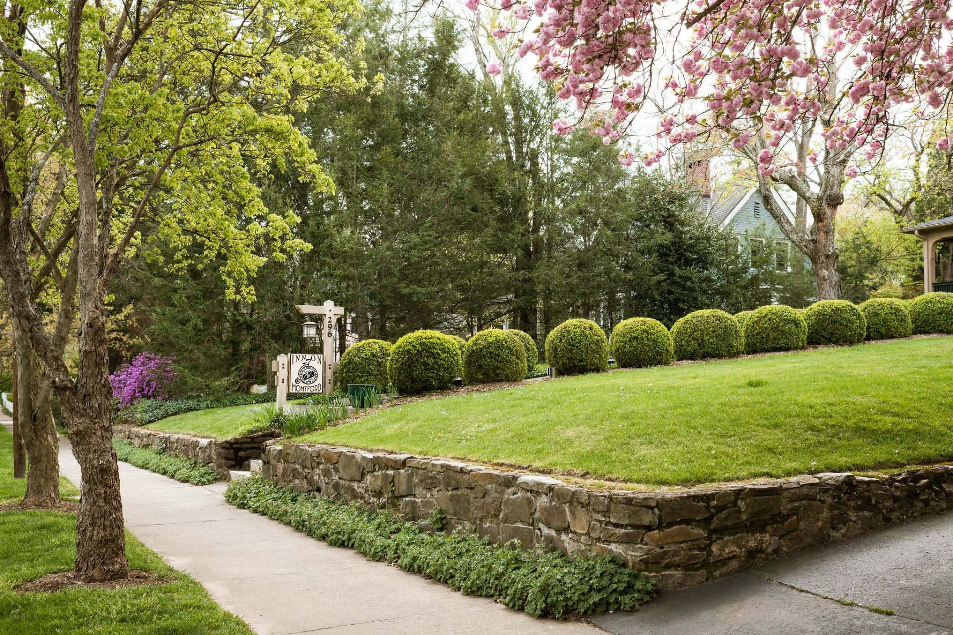 Sidewalk leading to Inn on Montford with a welcoming sign. Elevate front yard with a stone curb, green lawn and round ball bushes.