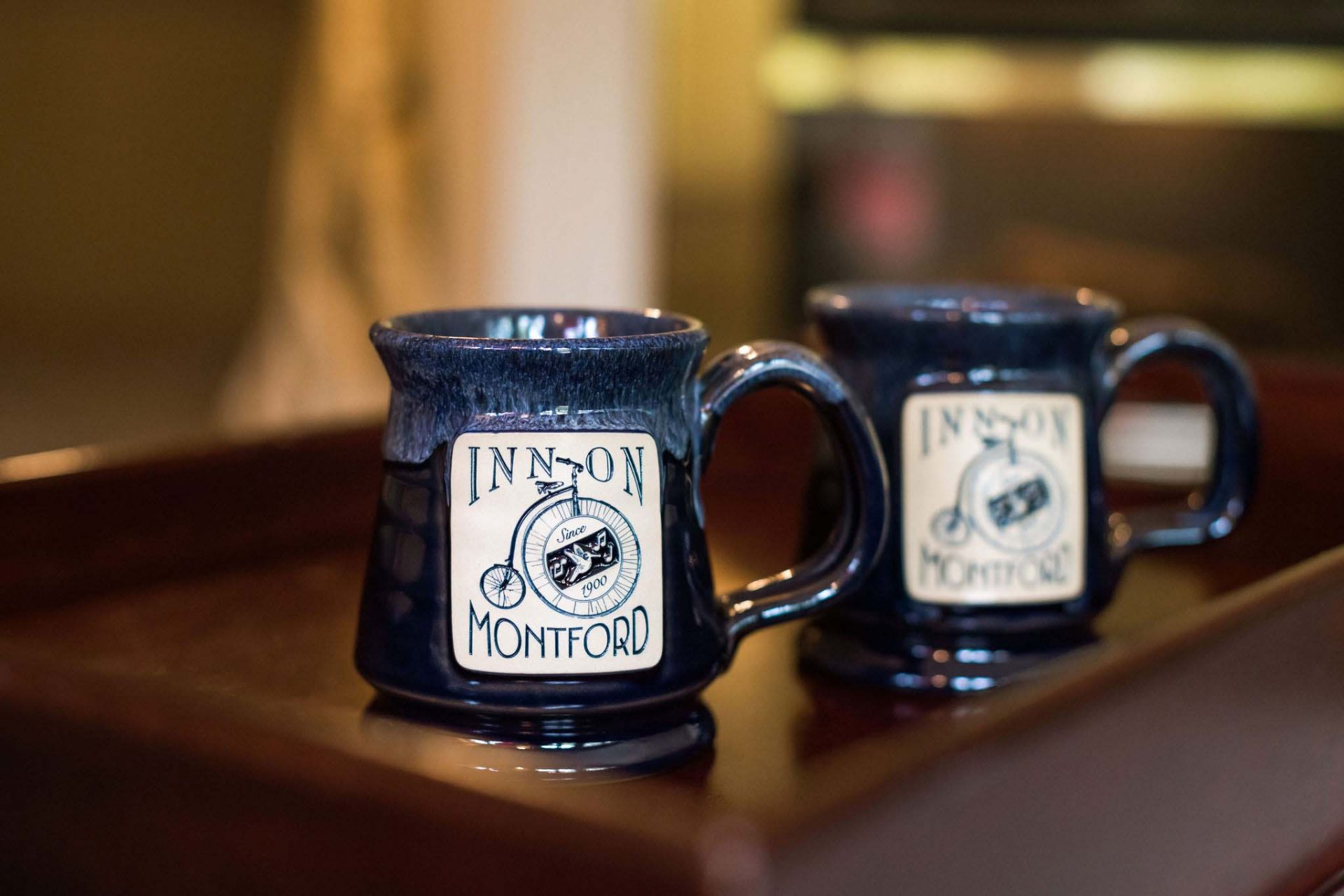 A cloesup of two dark blue clay mugs with the Inn on Montford logo.