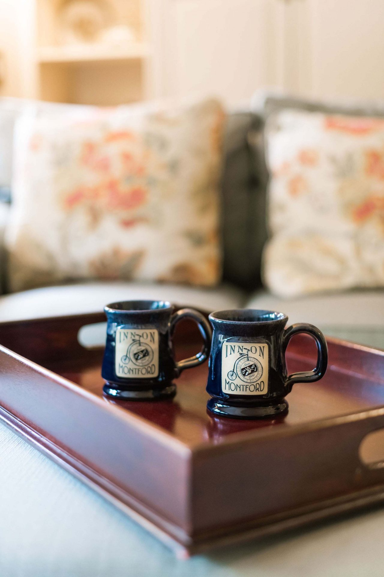 A wooden tray on a bed with two black mugs with the Inn on Montford logo.