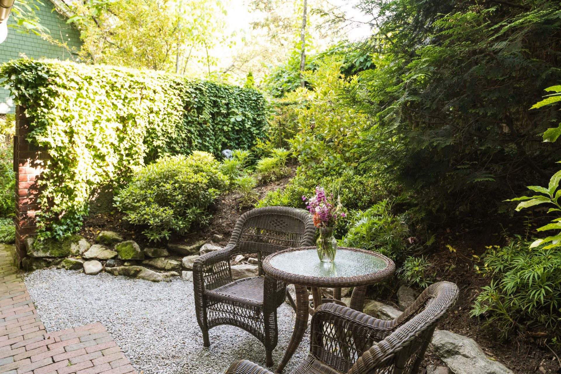 A small, enclosed backyard garden with a private entrance from one of the Asheville bed and breakfast rooms, with two chairs and a table.
