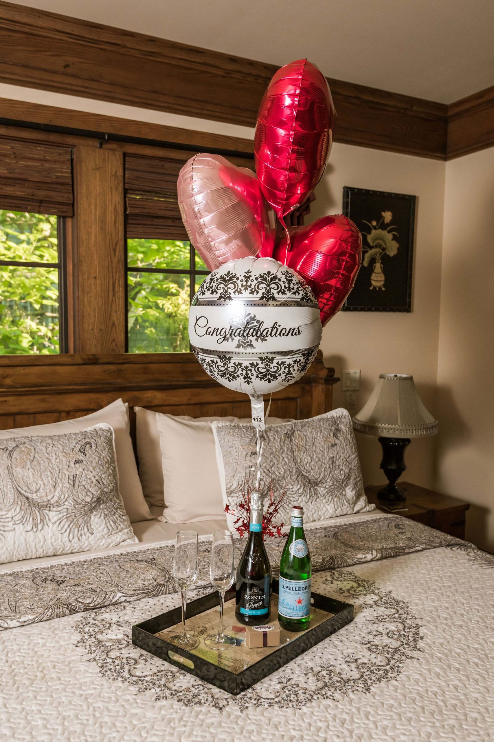 White and red heart-shaped balooons tied to a tray with a prosecco bottle, water bottle, chocolate truffles, and champagne glasses, arranged on a king bed.