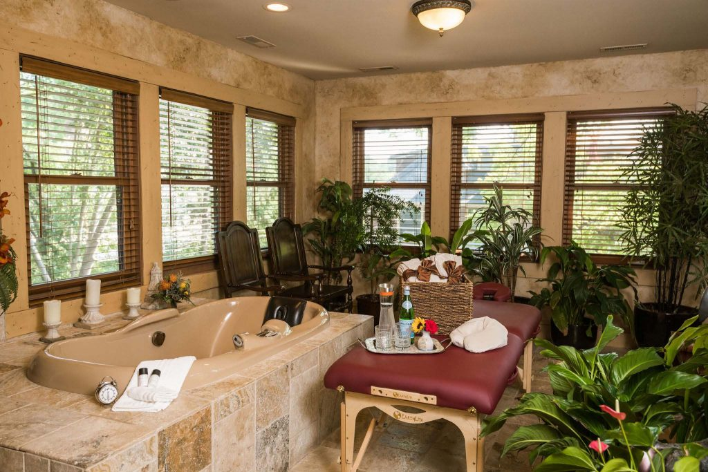 A spacious spa room with heated marble floors and a multi-jet two-person Whirlpool with shiatsu massage amd airbath. Room full of plants, with a massage table in the middle