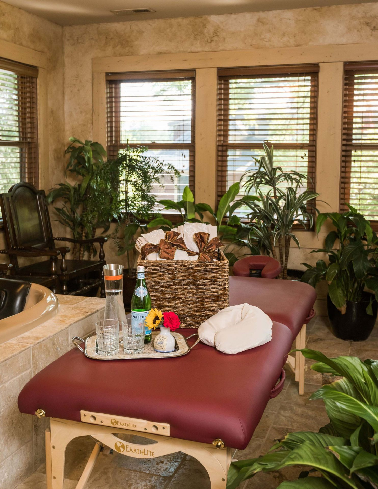 A massage table with a basket of folded towels, tray with a water bottle, caraffe, 2 glasses and a small flower bouquet. Massage therapy in a private bathroom full of plants.