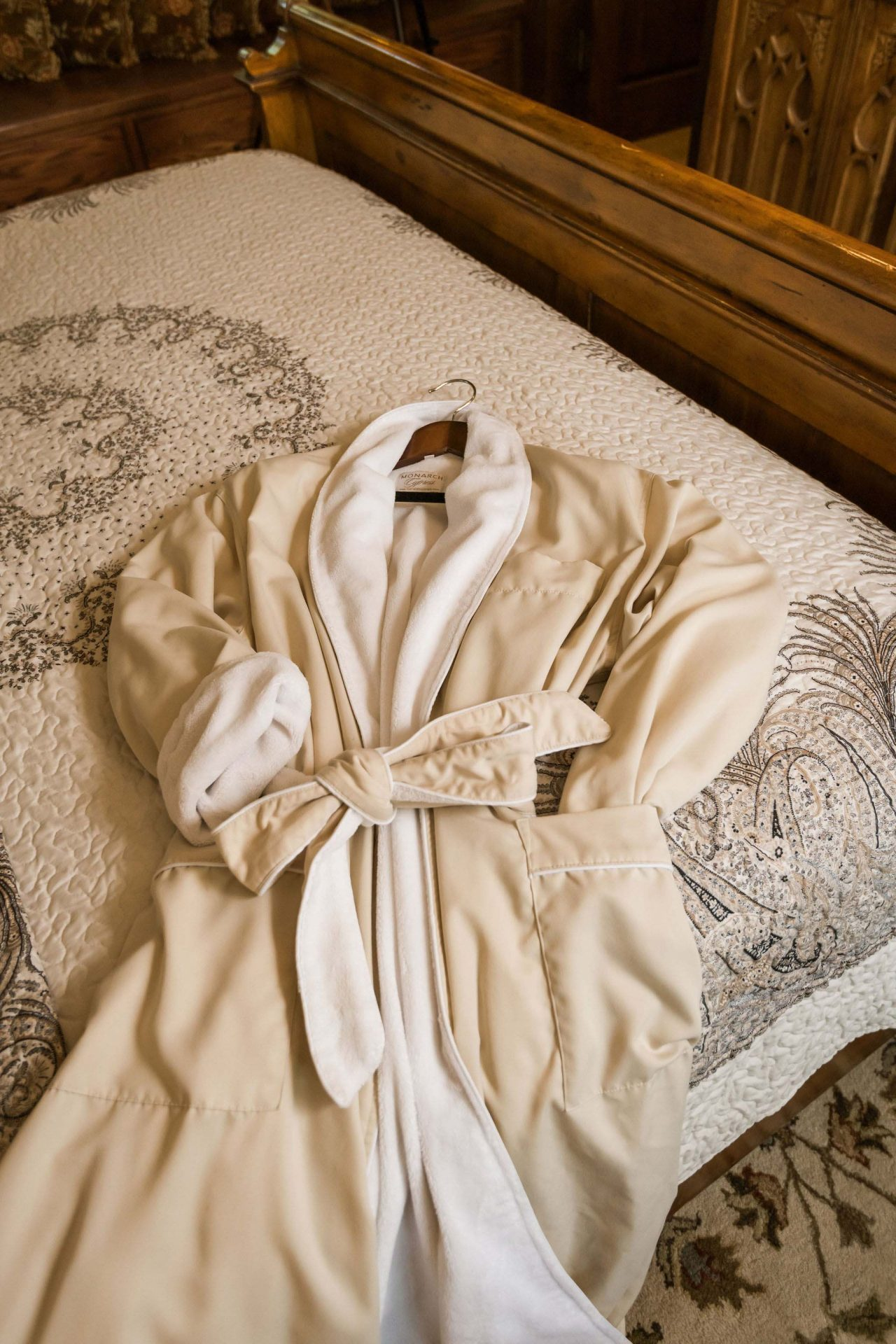 A warm, beige bathrobe lying on the bed in one of the bnb rooms.