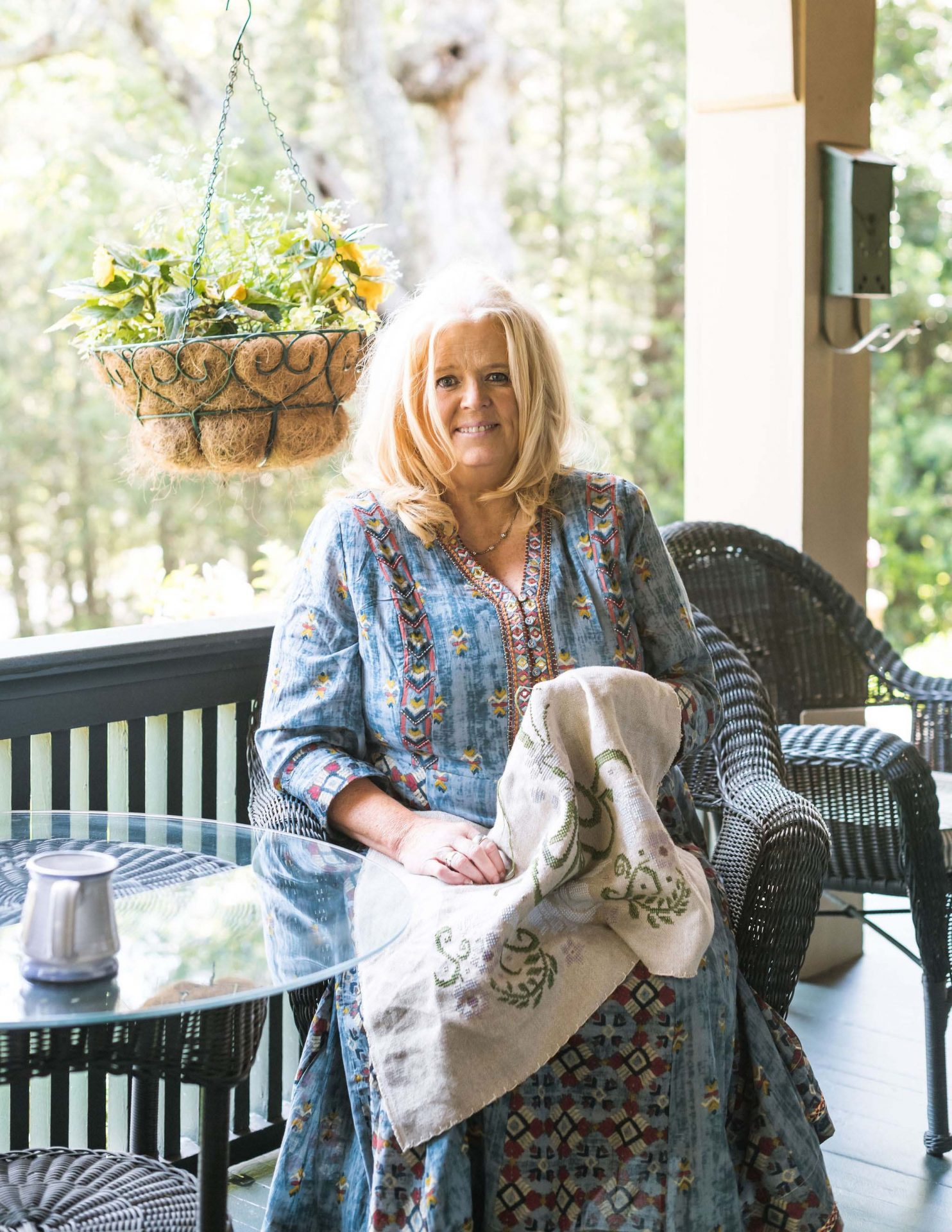 Shawnie embroidering on the porch, in a floral, long, blue dress. She is looking straight at the camera and smiling.
