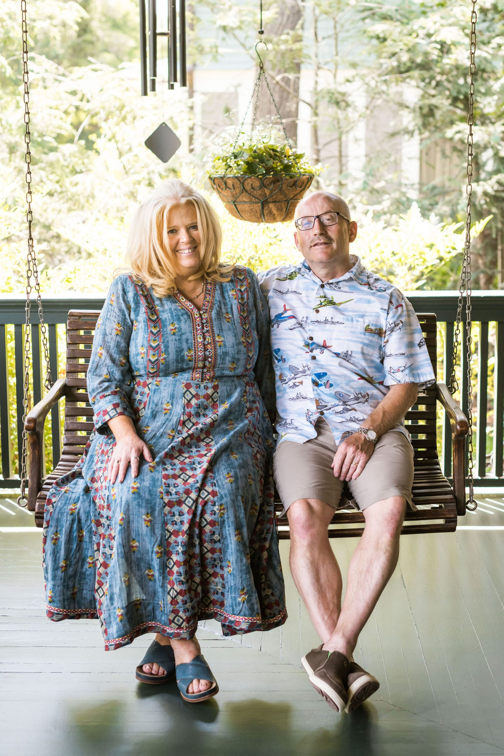 The Innkeepers sitting together on a swing on the porch and smiling. Shawnie weraing a long, floral dress, Willy wearing khaki shorts and a colorful, airplane-patterned shirt.