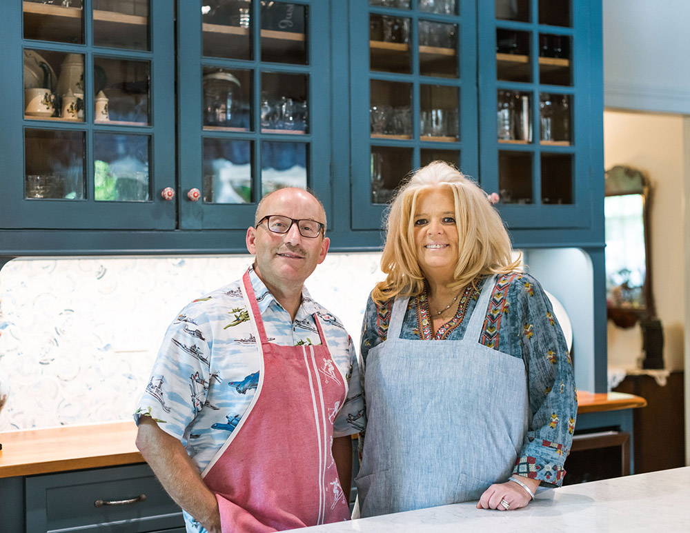 The Innkeepers standing together in the kitchen at a table. Both wearing aprons and smiling, blue cabinets with glass fronts in the background.
