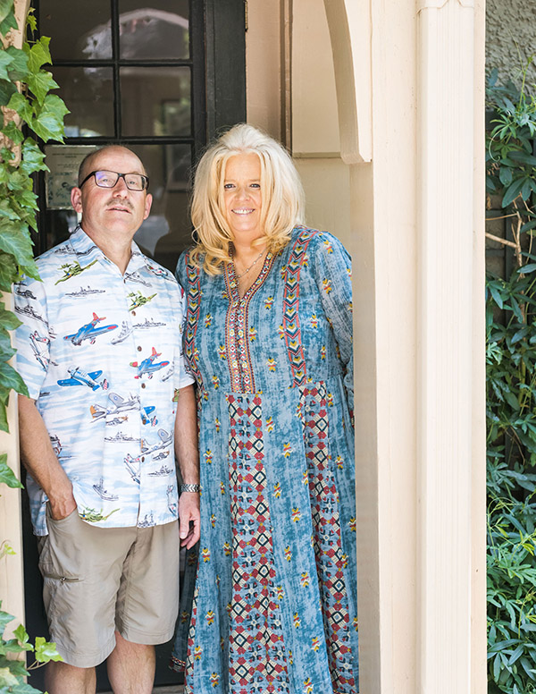 The Innkeepers standing at the back entrance to the main house. Shawnie is wearing a long, floral dress, and Willy khaki shorts and airplane-patterned shirt. Both are smiling.
