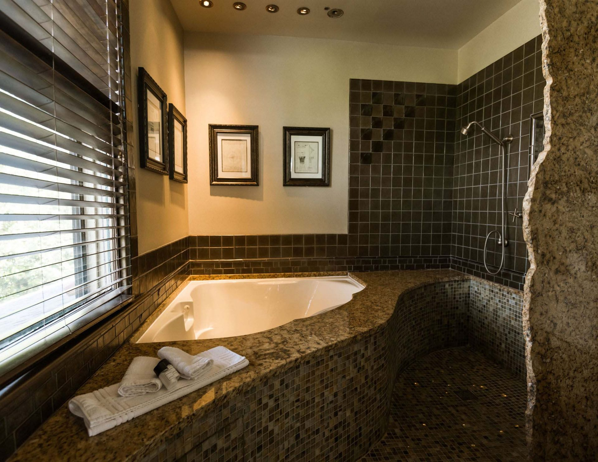 A two-Person jetted airbath tub with chromatherapy lights, marble countertops, and tiled floors. A romantic bath for a romantic Asheville getaway, captured in a dimmed light.
