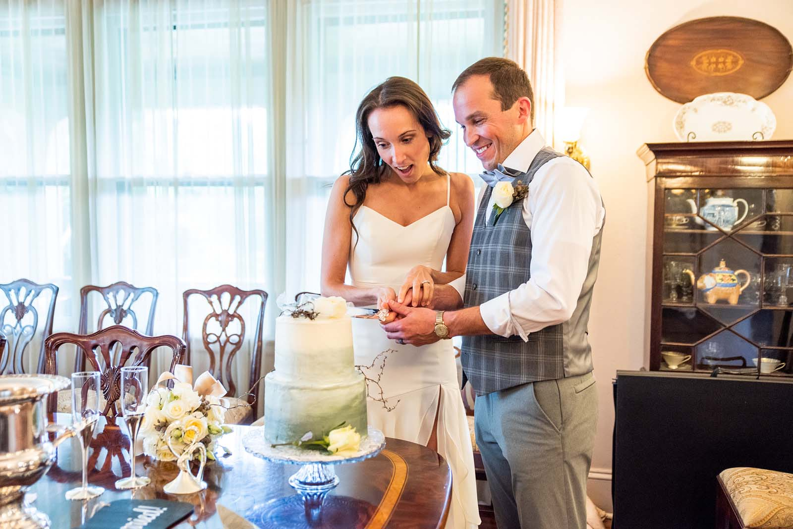 The newlyweds cutting together a cake in the dining room of the Asheville bnb during an intitmate wedding ceremony.