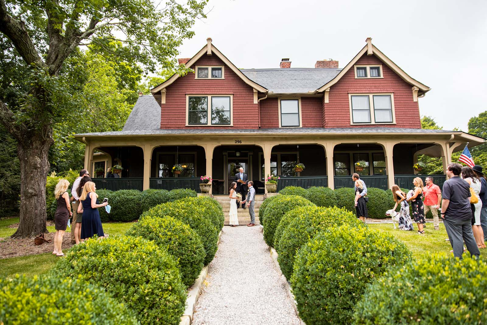 An intimate wedding ceremony at the Asheville bed and breakafst. The couple standing at the feet of the front porch, surrounded by guests scattered across the front yard.