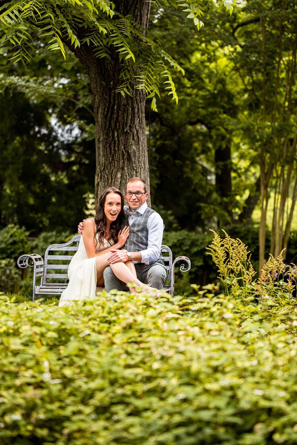 A wedding photoshoot in the gardens of the Inn on Montford. The couple is sitting on a garden bench, the bride is holding her legs on the groom's lap.