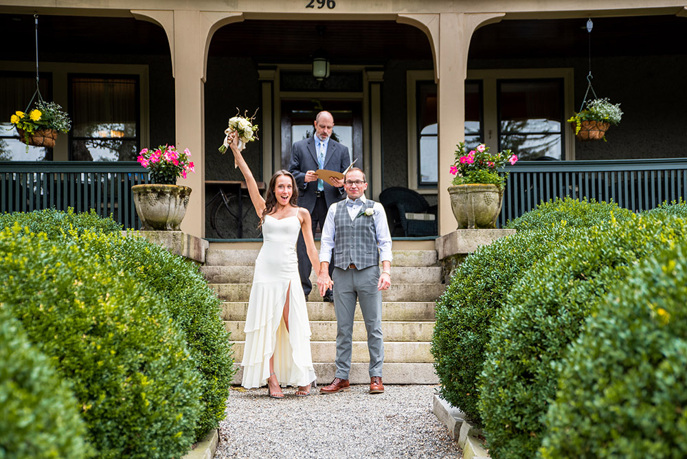 A newly wed couple holding hands, standing in front of the Inn, the bride is holding up a bouquet. Officiant standing in the background.