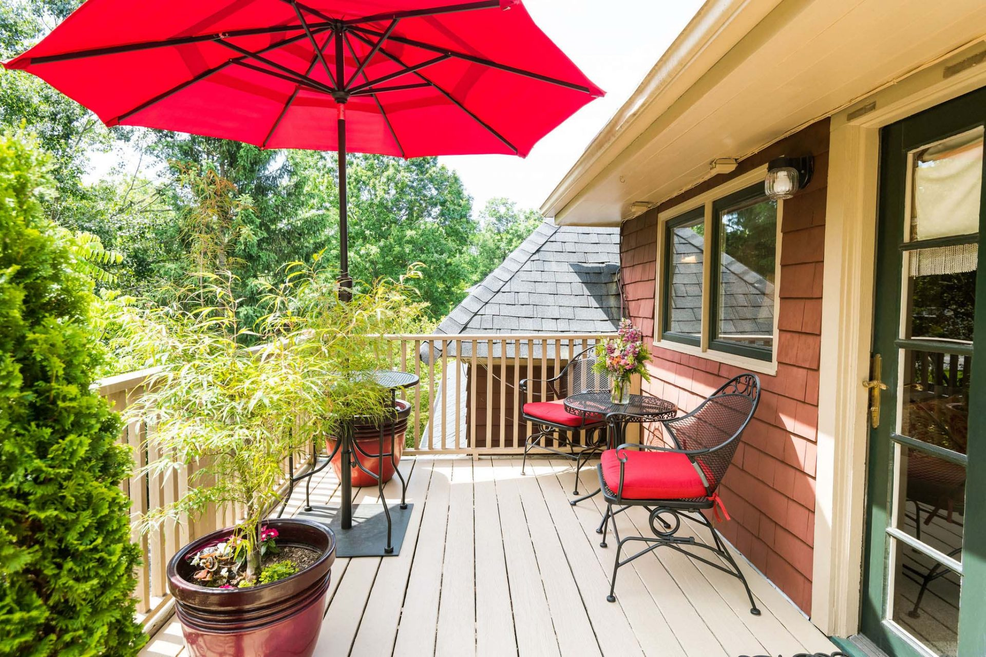 A private fenced upper deck with several plants, two chairs, small table, and a red sun garden umbrella.